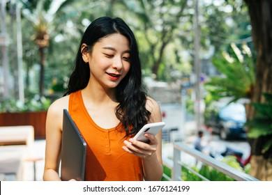 Portrait von Sexy asian schöne Frau mit orangefarbenem Hemd, das Laptop hält, sprechen auf dem Telefon in Café Garten in der Stadt.