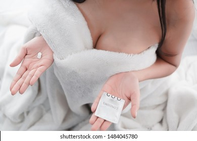 Portrait sexy asian woman with condom and contraceptive pill, safe sex concept