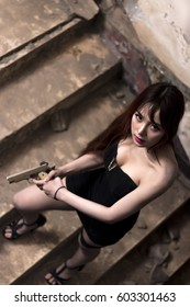 Portrait of Sexy Asian woman holding a handgun and posting in abandoned building, low key picture tone