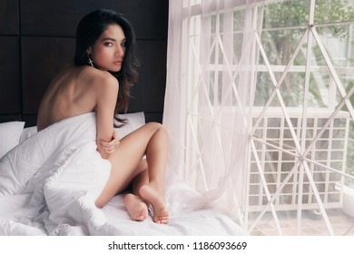 Portrait of sexy Asian woman on bed, nude concept.