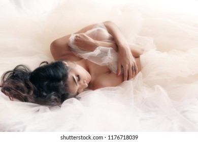 Portrait of sexy Asian woman posing on white bed