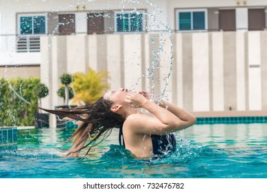 Portrait of sexy asian woman splash her hair in the swimming pool,thailand people