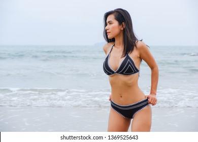 portrait sexy asian woman wearing bikini on the beach
