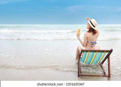 portrait of sexy asian young girl in bikini and hat sitting on deck chair at tropical beach and holding orange juice with beauty face on holiday vacation during happy time in summer