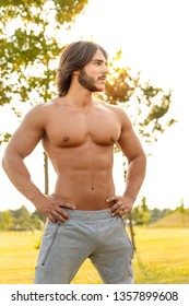 Portrait of a sexy athletic young man with strong muscles and wild macho attitude looking away during workout in the park in summer
