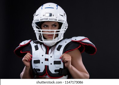 Portrait of sexy attractive young girl in a sports outfit for rugby with the helmet strongly looking forward standing on black background
