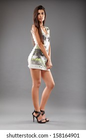 Portrait of sexy, beautiful indian woman in mini dress on gray background