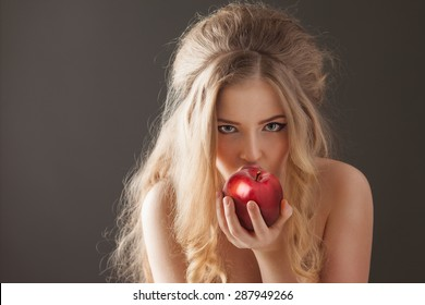 Portrait of a sexy beautiful nude pin-up girl from 60s or 70s, eating and biting a fresh red apple with temptation on dark background.