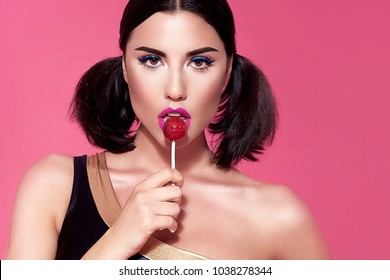 Portrait of sexy beautiful woman brunette hair style perfect bright make up mascara pink lipstick rouge background face care cosmetic accessory jewelry eat sweets lollipop candy diet mascara blush.