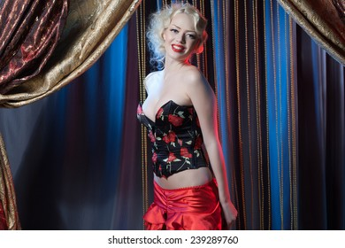 Portrait of a sexy beautiful woman posing in a studio over vintage background. Sexy cabaret dancer in retro style. Cabaret and pin-up concept.