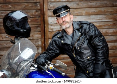 portrait of sexy biker dressed in black leather sitting on his bike