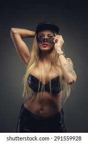 Portrait of sexy blond girl with tattoos. Isolated on grey background