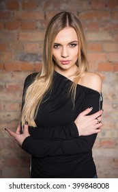 Portrait of sexy blond woman posing near brick wall