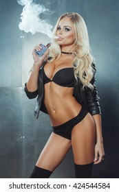 portrait of sexy blonde in black lingerie vaping e-cigarette against steel wall