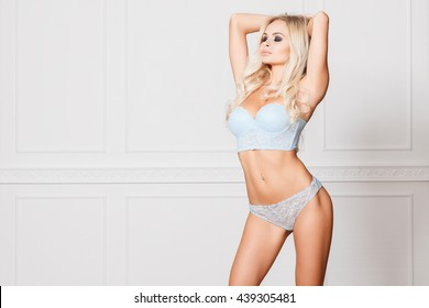 portrait of sexy blonde in blue lingerie with closed eyes posing against white wall
