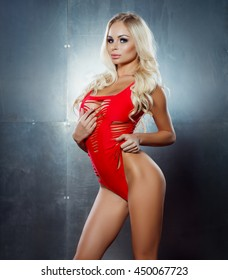 portrait of sexy blonde posing in red bodysuit posing against steel wall