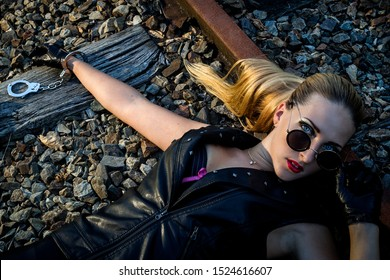 Portrait of a sexy blonde woman in black leather clothes with handcuffs and sunglasses. Gangsta girl with red lips lying on the abandoned railway at night.