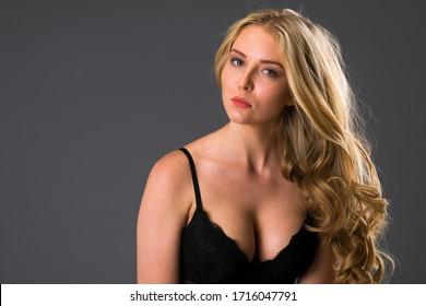 Portrait of sexy blonde woman in black underwear on a dark gray wall studio