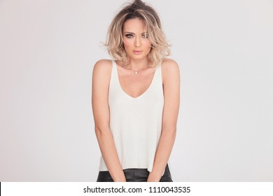 portrait of sexy blonde woman in undershirt standing on light grey background with hands together in front