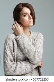 Portrait of sexy brunette girl in sweater, costs on a gray background