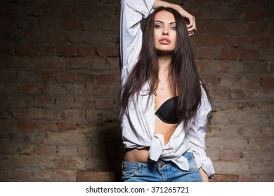 Portrait of sexy brunette posing in black bra and white shirt