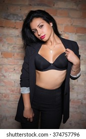Portrait of sexy brunette wearing black clothes posing near the wall