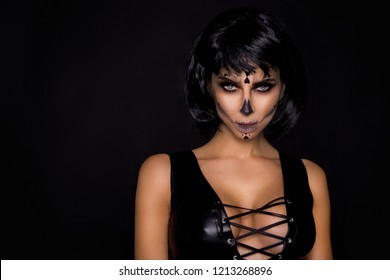 Portrait sexy brunette woman in Halloween makeup  on a black background in the studio. Make-up skeleton, monster and witch
