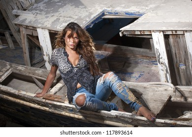 portrait of sexy brunette woman posing in from of shipwreck