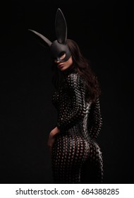 portrait of sexy brunette woman posing in rabbit black mask and bodysuit back shot big ass
