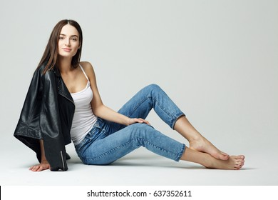 Portrait of a sexy brunette woman in studio on a grey background