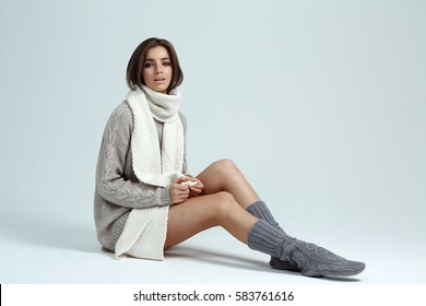 Portrait of sexy brunette woman in sweater, sits on floor on a grey background