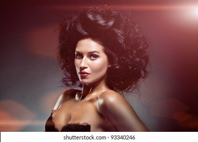 Portrait of sexy caucasian young woman with beautiful black hair posing on dark background