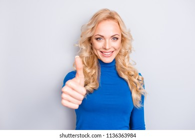 Portrait of sexy, cheerful, stylish, pretty, cute, charming, nice, blonde woman in blue turtleneck showing thumb up sign front to the camera isolated on grey background
