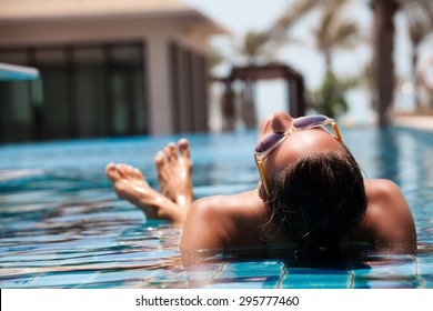 Portrait of sexy cheerful woman relaxing at the luxury poolside.  Girl at travel spa resort pool. Summer luxury vacation.