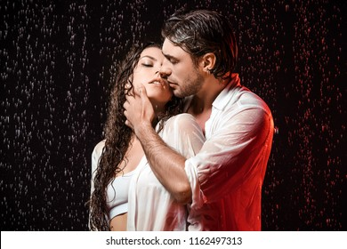 portrait of sexy couple in white shirts standing under rain on black backdrop