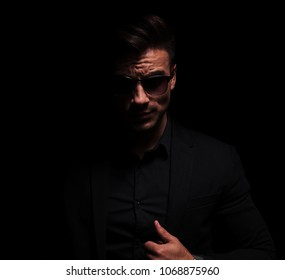 portrait of sexy and dark fashion man with sunglasses pulling his black suit collar, on black background