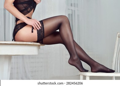 Portrait of sexy fashion model girl indoors. Beautiful lady in elegant black panties and stockings. Beauty brunette woman with attractive buttocks in lace lingerie. Female ass in underwear. Naked body