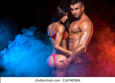 Portrait of sexy and fit woman wear red lingerie and hugging handsome fitness man in black suit