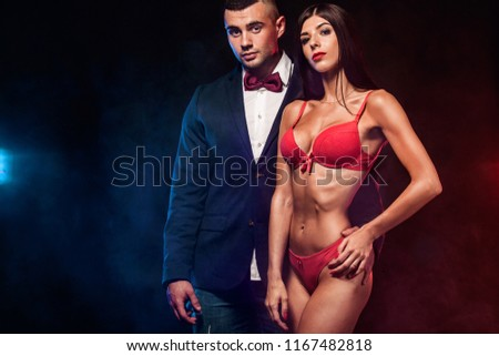 6a569cacd1 Portrait of sexy and fit woman wear red lingerie and hugging handsome  fitness man in black