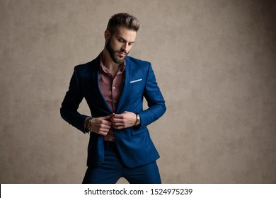 portrait of sexy formal business man wearing a navy suit standing and fixing his jacket while looking down seductive against gray studio background