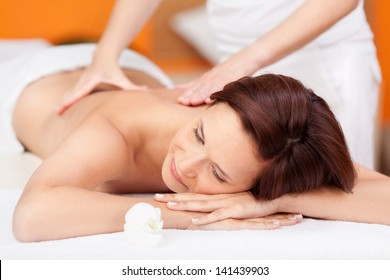 Portrait of sexy fresh woman in spa salon getting massage