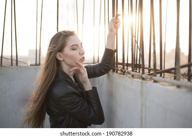 Portrait of sexy girl dreaming and  posing  of concrete and rusty metallic wall and sun set sky  background Serious woman in black leather jacket  looking down on roof