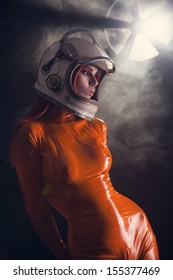 Portrait of sexy girl in orange latex catsuit and space helmet, sci-fi setting