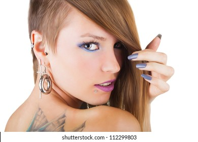 Portrait of a sexy girl with piercings and tattoo on her back on white background