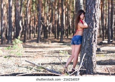 portrait of sexy girl posing in the tree roots at the sand. nature background