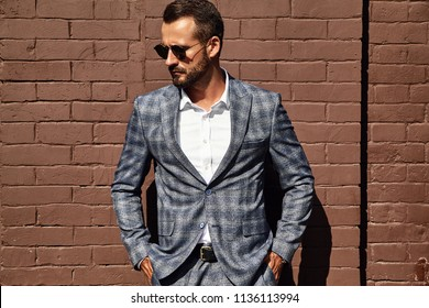 Portrait of sexy handsome fashion businessman model dressed in elegant checkered suit posing near brick wall on the street background. Metrosexual