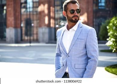 Portrait of sexy handsome fashion businessman model dressed in elegant blue suit posing on street background. Metrosexual
