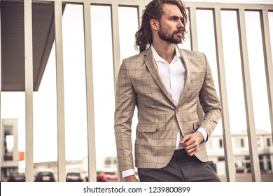 Portrait of sexy handsome fashion businessman model dressed in elegant checkered suit posing near brick wall on the street background. Long haired Metrosexual