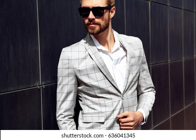 portrait of sexy handsome fashion male model man dressed in elegant white checkered suit 