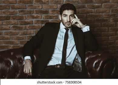 Portrait of a sexy handsome man on a leather sofa. Luxurious lifestyle. Fashion shot. Men's clothing and accessories.
